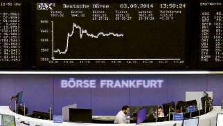 Traders are pictured at their desks in front of the DAX board