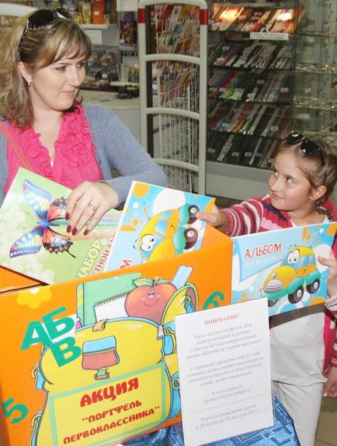 Мама с дочкой выбирают альбом для рисования в магазине