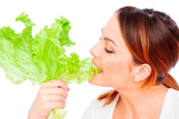 Девушка кусает свежие листья салата