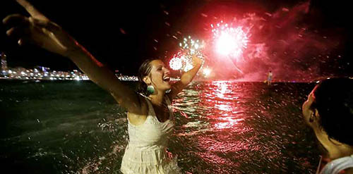 Revellers celebrated as fireworks exploded during New Year festivities on Copacabana Beach, Rio de Janeiro