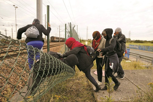 Migrants make their way across a fence near train tracks as they attempt to access the Channel Tunnel